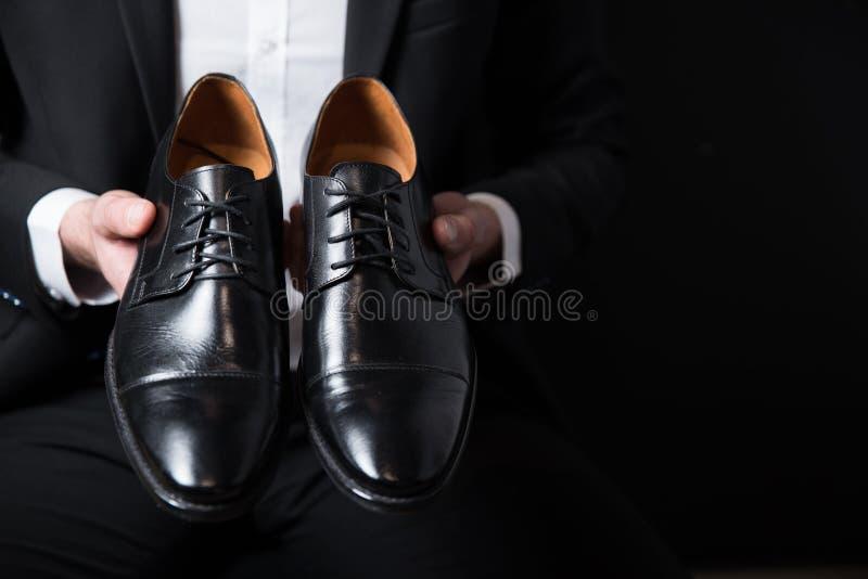 Schwarze Schuhe auf Geschäftsmannhand stockbilder