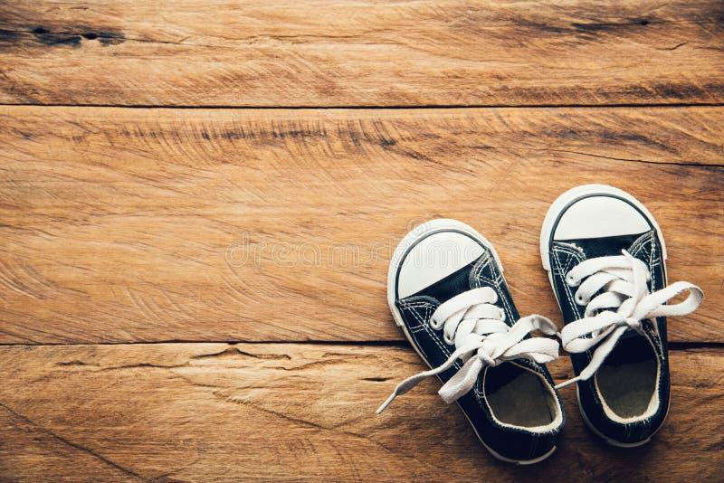Schwarze Schuhe für Kinder auf Bretterboden für Lebensstil lizenzfreie stockbilder