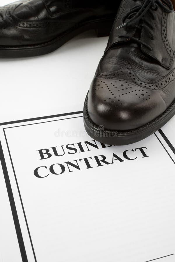 Schwarze Schuhe und Geschäftsvertrag lizenzfreie stockfotografie
