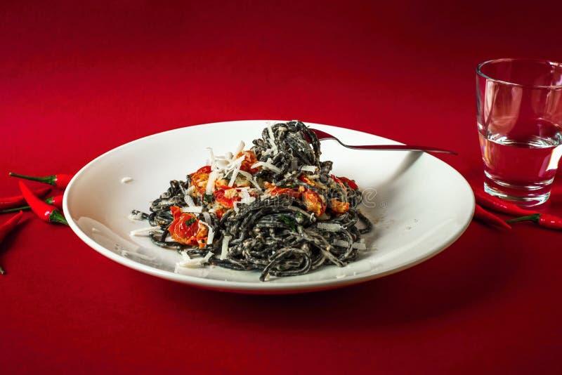 Schwarze Spaghettis mit gebratener Tomate, Pfeffern der heißen Paprikas, Ricotta und Parmesankäseparmesankäse auf weißer Platte stockfotos