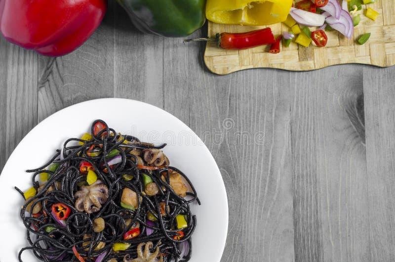 Schwarze Spaghettis mit Gemüse in der Platte auf der Draufsicht des Naturschwarzweiss-Hintergrundkopienraumes lizenzfreie stockfotografie