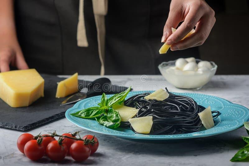Schwarze Spaghettis mit Kopff??ertinte Mädchen besprüht Scheiben des bereiten Abendessens des Parmesankäseparmesankäses Köstliche lizenzfreies stockfoto