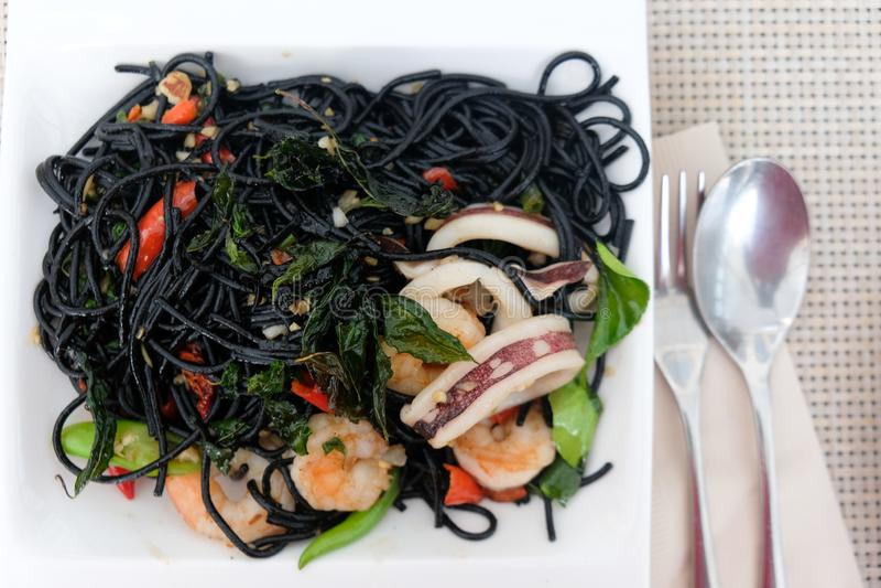 Schwarze Spaghettis mit Meeresfrüchten und Gemüse auf Platte lizenzfreie stockbilder