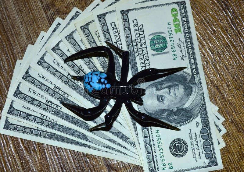 Schwarze Spinne sitzt auf hundert Dollarscheinen stockbilder