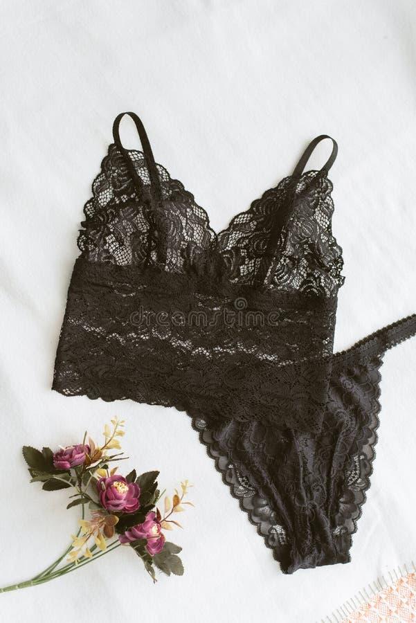 schwarze Spitzeunterwäsche liegt auf dem hellen Bett Erotische Wäschehauptlügen auf einem hellen Hintergrund nahe bei den Blumen  lizenzfreies stockfoto