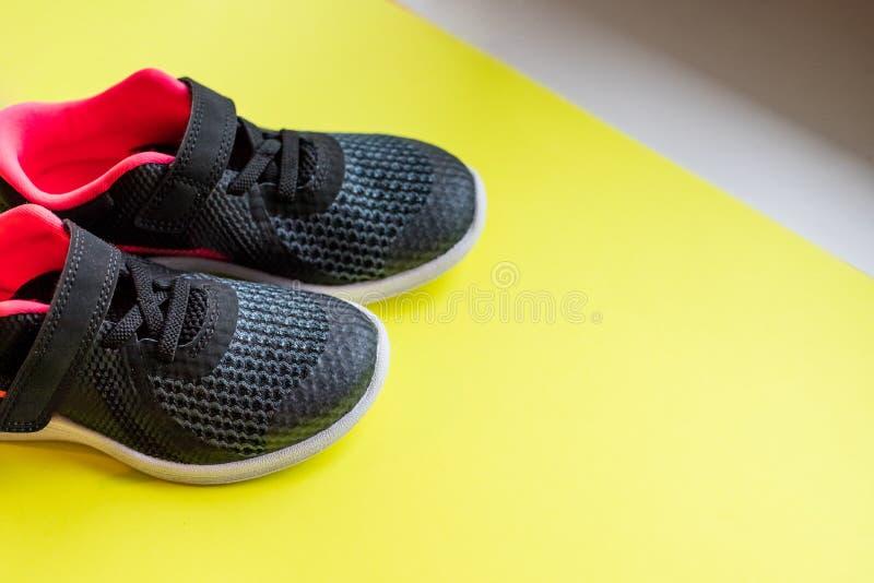 Schwarze Sportschuhe für das Laufen auf gelbem Hintergrund lizenzfreie stockfotografie