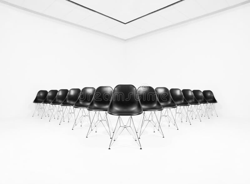 Schwarze Stühle in einem weißen Raum stockfotografie