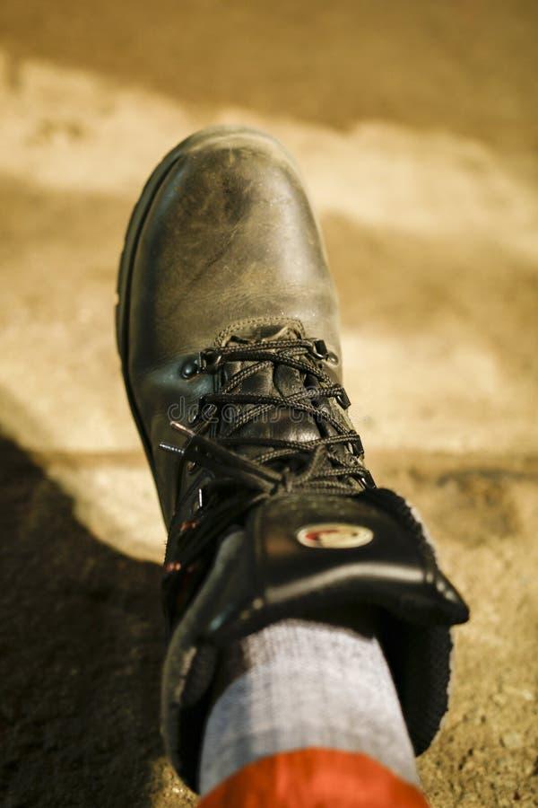 Schwarze Stiefel, schwarze Spitze, liegend auf dem Boden mit orange Hosen lizenzfreie stockfotografie