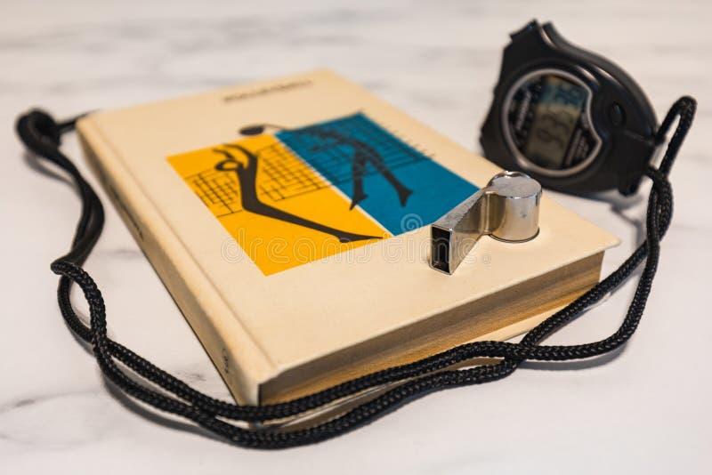 Schwarze Stoppuhr, Ausbildungsbuch und Pfeife auf einer Marmorplatte lizenzfreie stockfotos