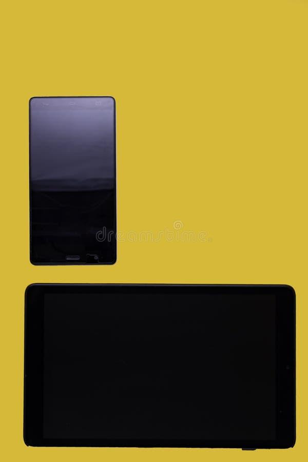 Schwarze Tablette und Smartphone auf gelbem Hintergrund lizenzfreie stockbilder