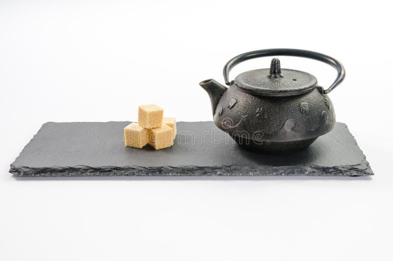 Schwarze Teekanne des Gusseisens und vier Rohrzuckerwürfel dazu auf Rekta stockfotos
