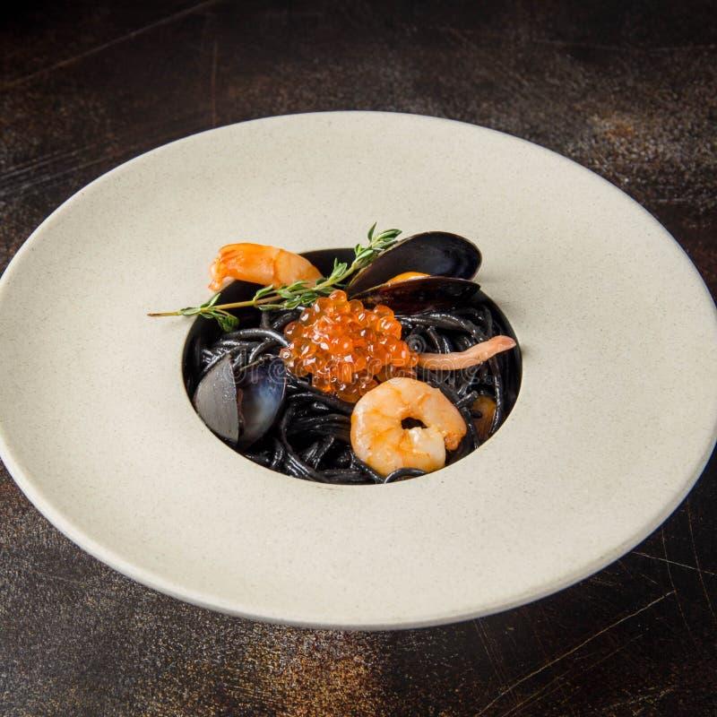 Schwarze Teigwaren Nero mit Meeresfrüchten, Spaghettis mit Garnele, Kalmar und rotem Kaviar Schöner geschmackvoller Teller lizenzfreie stockfotos