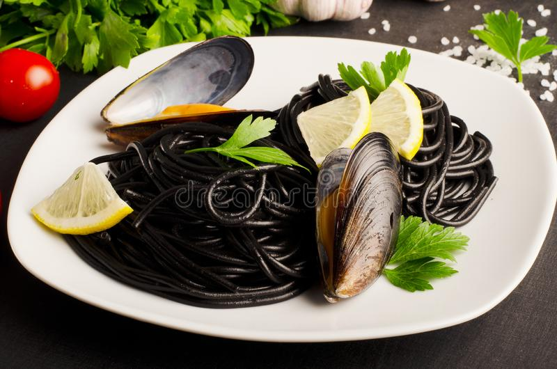 Schwarze Teigwarenspaghettis der Meeresfrüchte mit Miesmuscheln auf weißer Platte auf dunklem Hintergrund lizenzfreie stockfotos