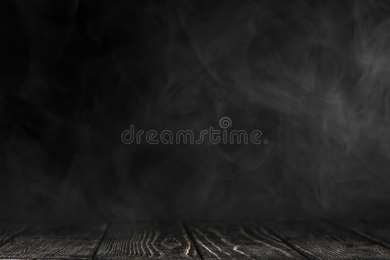 Schwarze Tischplatte auf einem schwarzen Hintergrund mit weißem Rauche stockbild