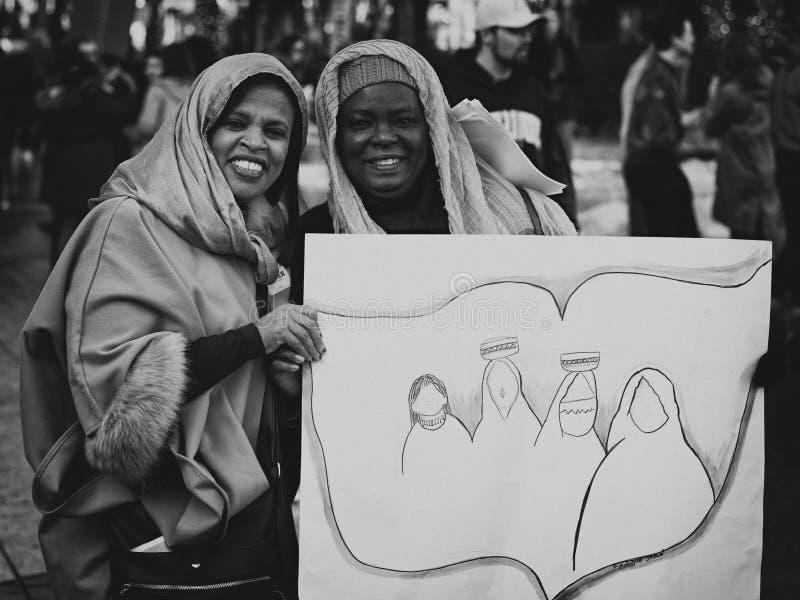 Schwarze und arabische Frauen, die Plakat halten lizenzfreie stockbilder
