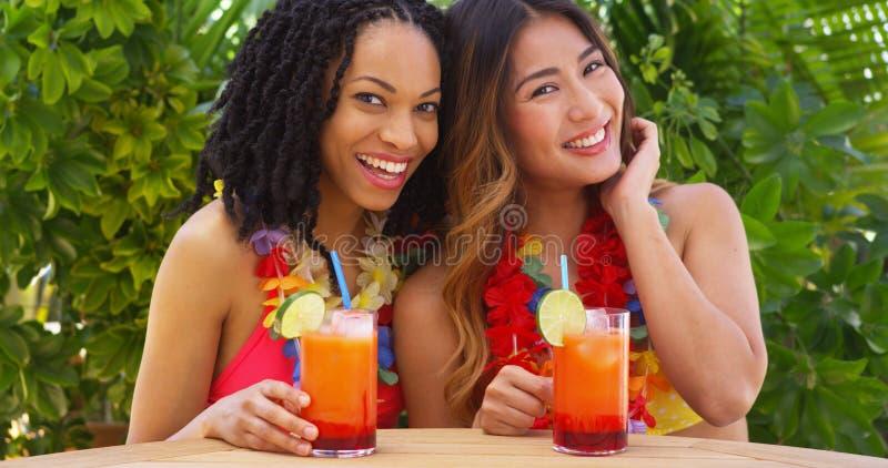 Schwarze und asiatische beste Freunde, die zusammen tropische Ferien genießen stockfotografie