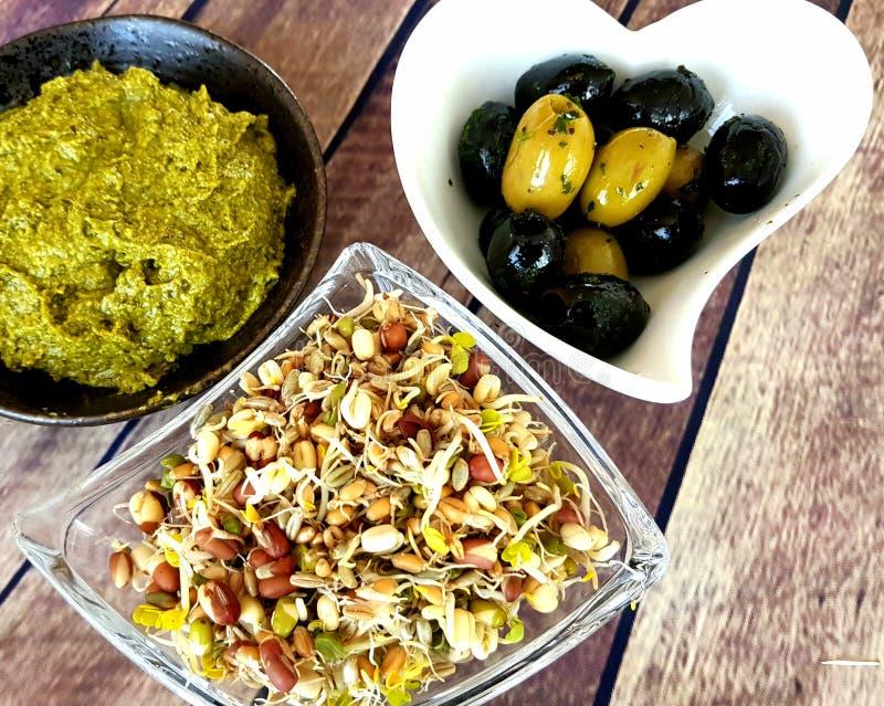 Schwarze und grüne Oliven, Pesto und Sprösslinge von unterschiedlichen Weizenernten und -gemüse stockbild