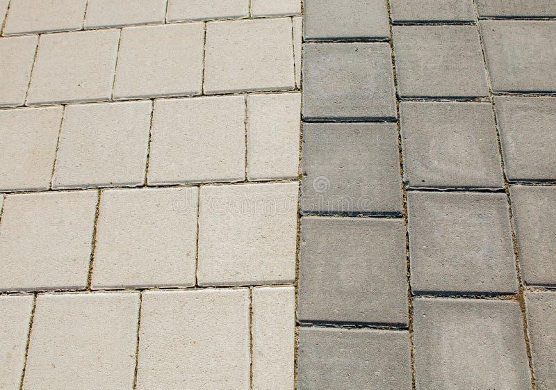 Schwarze und graue Kopfsteine eines Fußwegs sind in ein geometrisches Muster gelegt worden Sie werden mit Zeit getragen lizenzfreie stockbilder