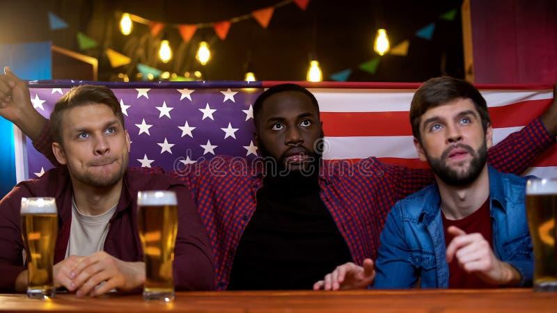 Schwarze und kaukasische Freunde unglücklich mit verlierendem Match des amerikanischen Teams, Zeit in der Kneipe lizenzfreie stockfotografie