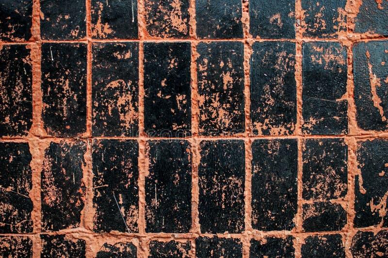 Schwarze und orange Wand deckt Beschaffenheitshintergrund mit Ziegeln stockfotos