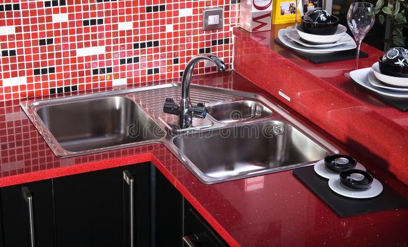 Schwarze und rote Gegenspitze in der Küche Whitwanne lizenzfreies stockfoto