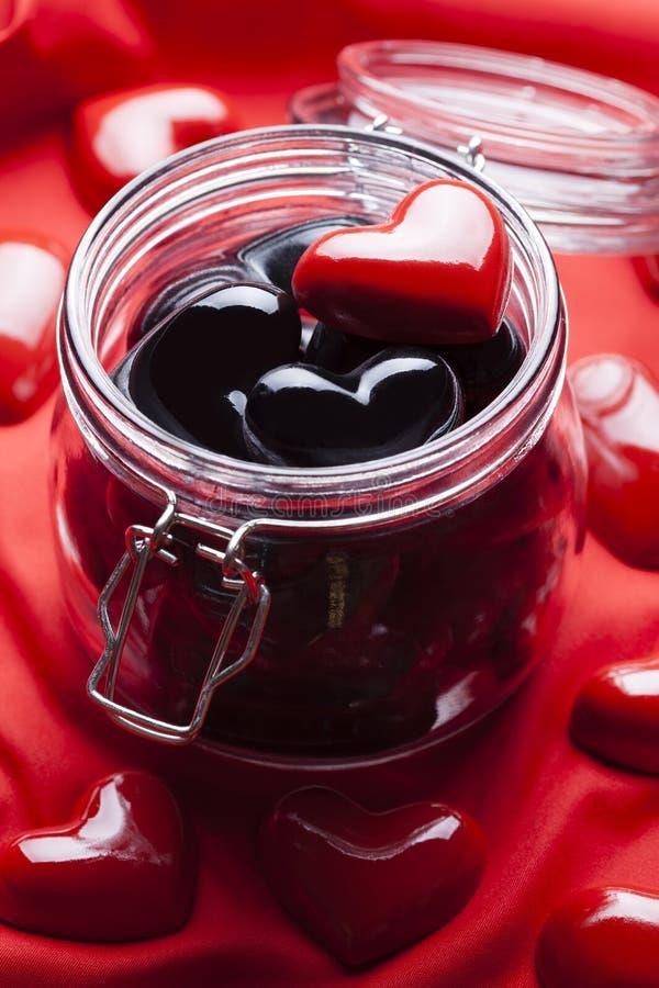 Schwarze und rote Herzen im Glas stockfotos