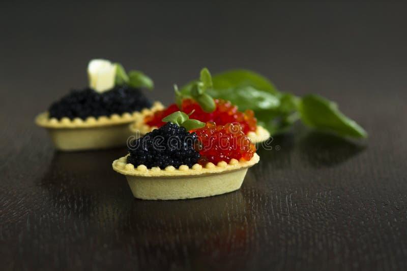 Schwarze und rote Kaviar Tartlets lizenzfreie stockfotos