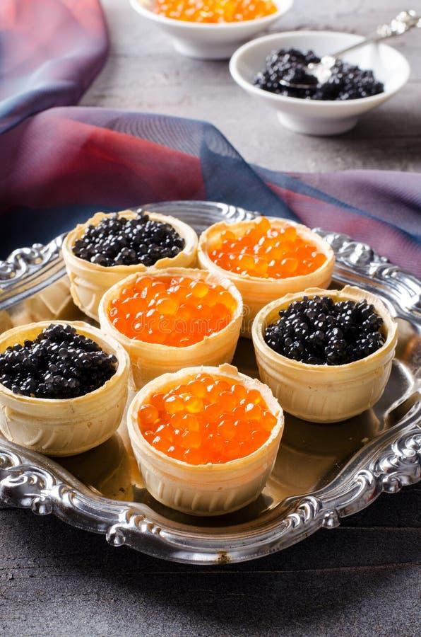 Schwarze und rote Kaviar Tartlets, Aperitif Canapes auf Silbertablett stockbilder