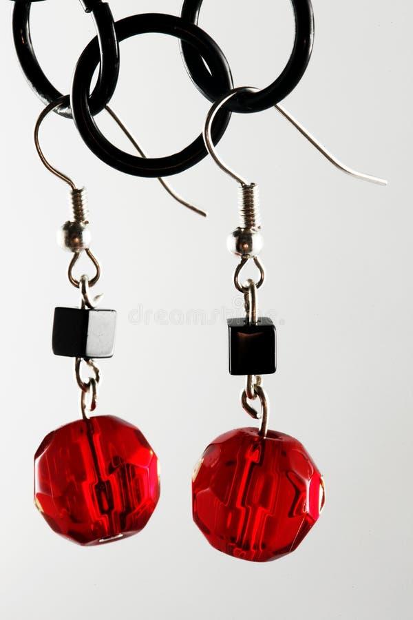 Schwarze und rote Ohrringe stockfotos