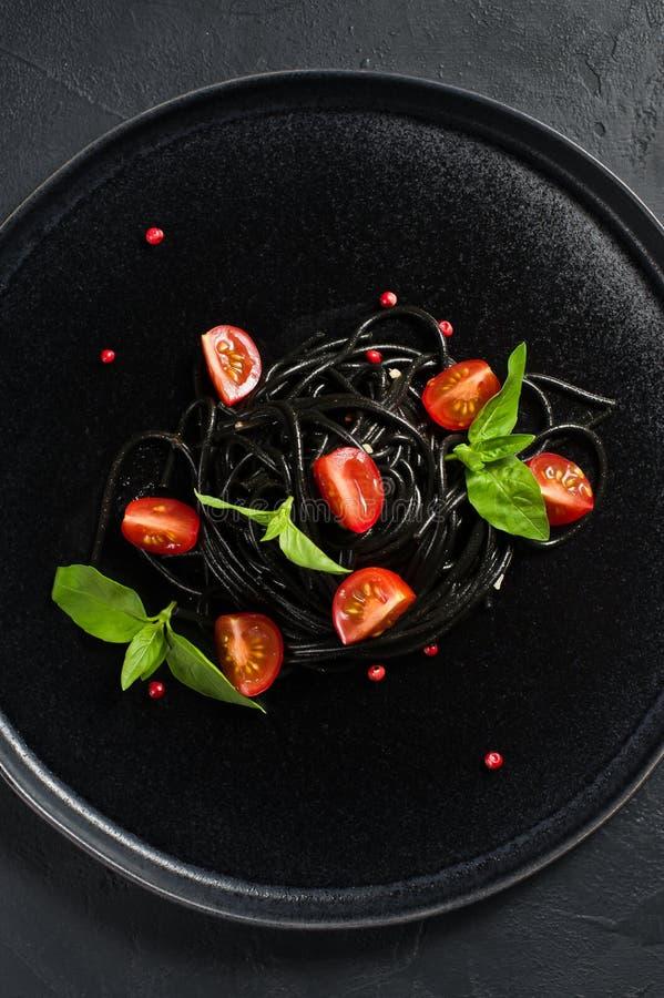 Schwarze vegetarische Teigwaren mit Basilikum- und Kirschtomaten Schwarzer Hintergrund, Draufsicht stockfotografie
