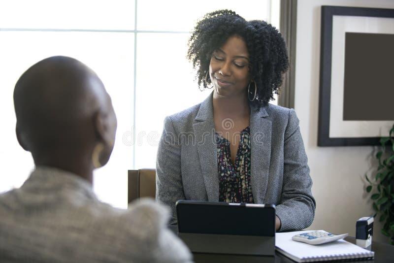 Schwarze weibliche Geschäftsfrau oder Manager Arguing mit Angestelltem lizenzfreie stockfotografie