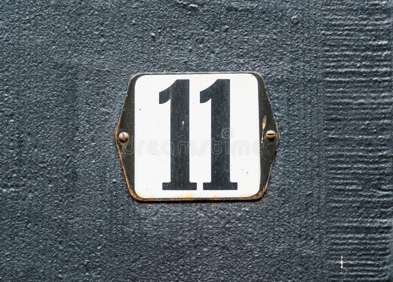 Schwarze Zahl der Hausnummer 11 auf weißer Platte stockfotografie