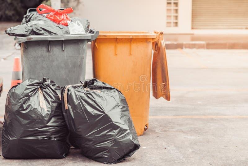 Schwarzer Abfall der Plastiktaschen des Abfalls, Verschmutzung, Loskramdump, bereiten grünen gelben Behälter auf stockfoto
