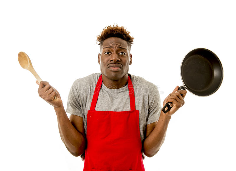 Schwarzer afroer-amerikanisch Mannausgangskoch im Chefschutzblech die Wanne und Löffel kochend verloren und überbelastet stockfotografie
