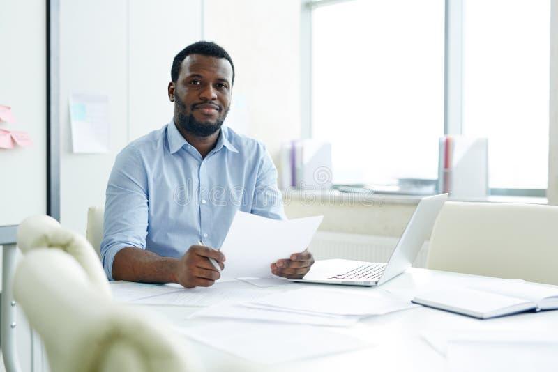 Schwarzer Angestellter, der im Büro mit Papieren sitzt lizenzfreie stockfotografie