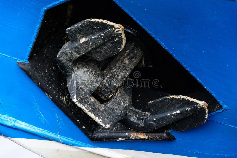Schwarzer Anker auf dem Bogen des blauen Bootes lizenzfreie stockbilder