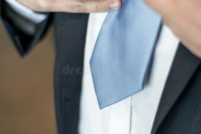 Schwarzer Anzug, weißes Hemd und blaues Bindung Geschäfts-, Finanz- oder diplomatischeskonzept übergibt oben binden stockfotografie