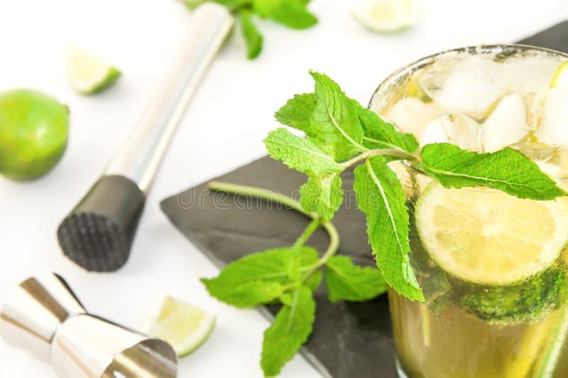 Schwarzer Behälter mit mojito Cocktail, Getränk, das Werkzeuge, Kalk, Minze herstellt lizenzfreie stockfotografie