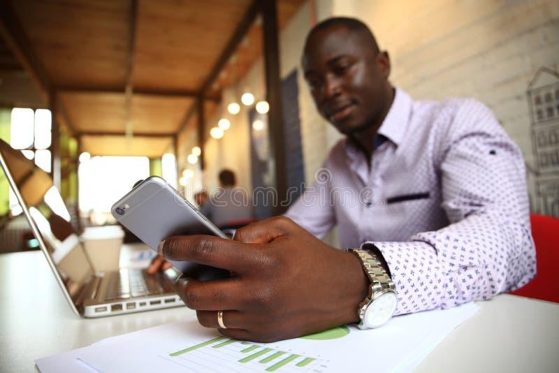Schwarzer Berufsgeschäftsmann in der Geschäftsgesellschaftskleidung auf mobilem Zellensmartphone stockfoto