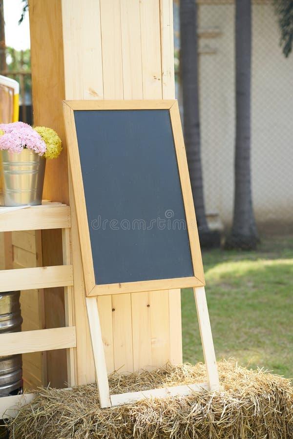 Schwarzer Brettstand auf Stroh verzieren mit Blumenvase lizenzfreies stockfoto