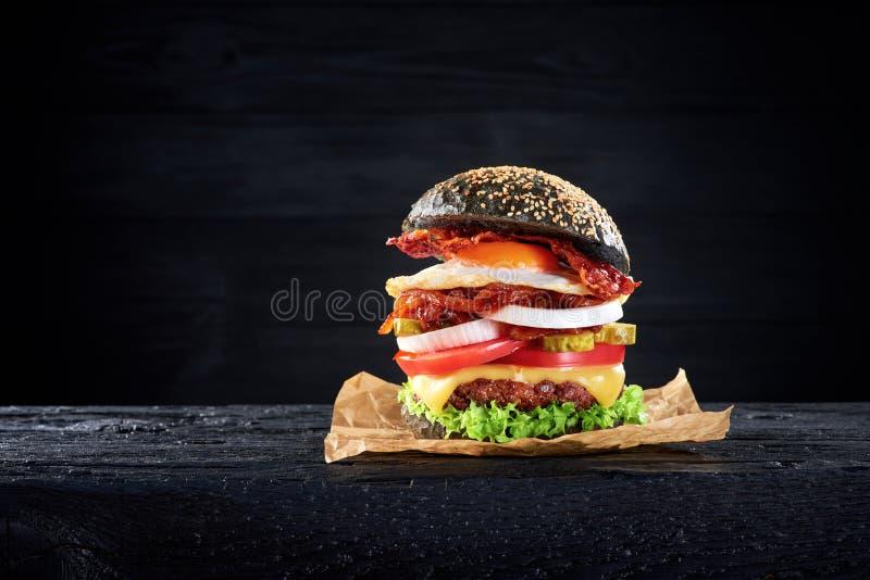 Schwarzer Burger mit Ei und Speck auf schwarzem Holztisch stockfotos