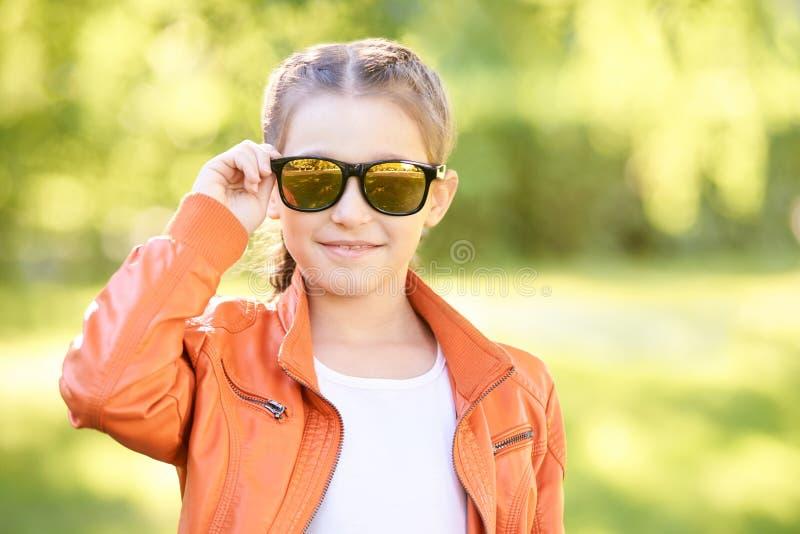 Schwarzer Eyewear Farbjacke auf Straße jugendlich Lebensstil des Zaubers jugendlicher flippiger Felsen weiblicher Brunette stockfotografie