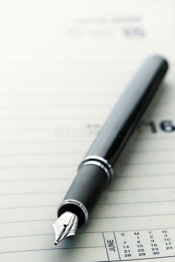 Schwarzer Füllfederhalter auf Tagebuch stockbilder