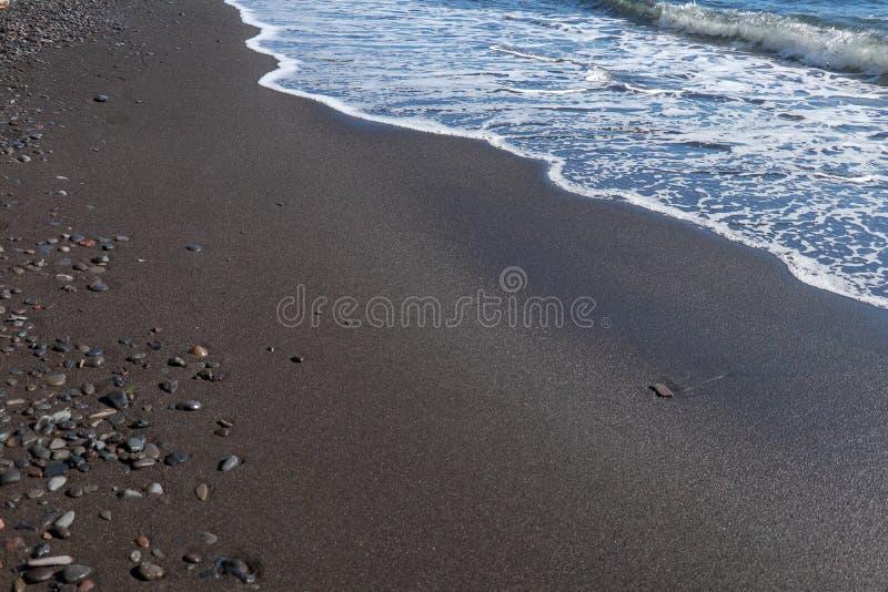 Schwarzer feiner vulkanischer Sandstrand und -kiesel auf Bali-Insel in Indonesien Das Meerwasser erreicht die Küste und die Drehu lizenzfreies stockbild