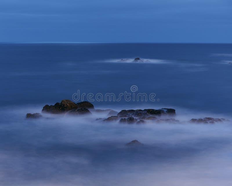 Schwarzer Felsen an der blauen Stunde auf dem Ozean Ruhig, weich und kalt stockfoto