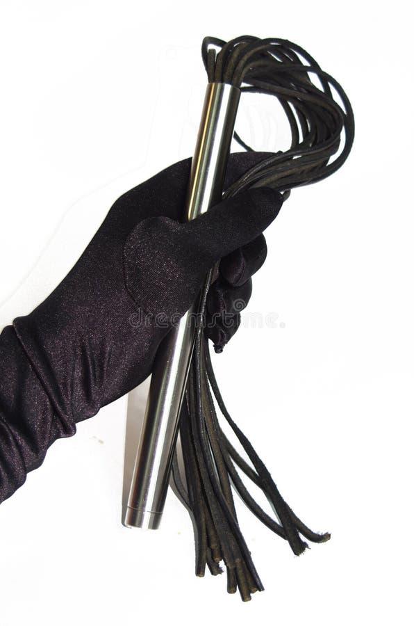 Schwarzer Fetisch, der Peitsche in der Frauenhand prügelt stockfotografie