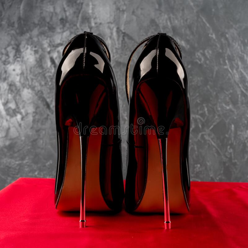 Schwarzer Fetisch glänzender Lackstiletto mit hohen Fersen mit Knöchelgurt lizenzfreies stockfoto