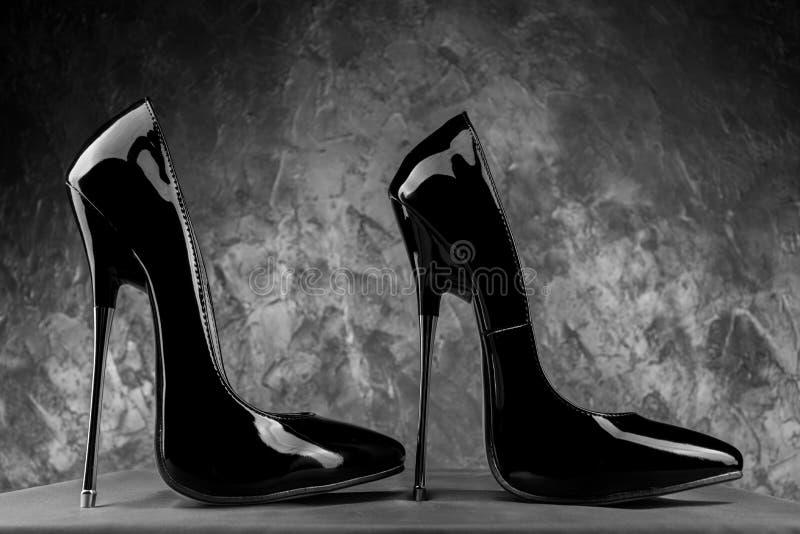 Schwarzer Fetisch glänzender Lackstiletto mit hohen Fersen mit Knöchelgurt stockfotografie