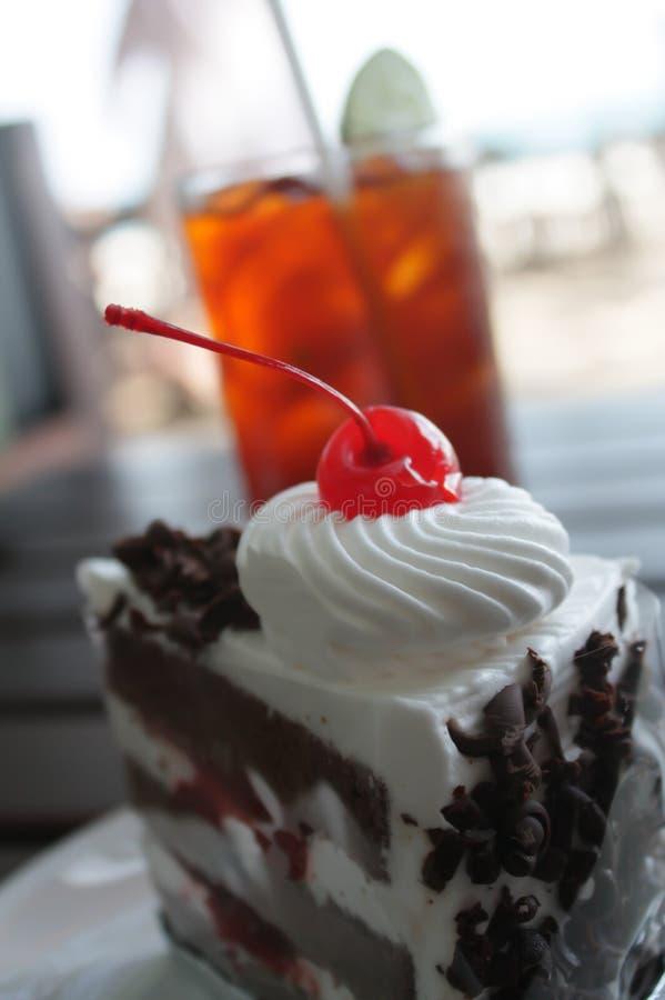 Schwarzer Forest Cake, Bäckerei mit Sahne verziert, Schokolade, Kirsche auf weißer Platte und Kalk-Eis-Tee lizenzfreies stockfoto