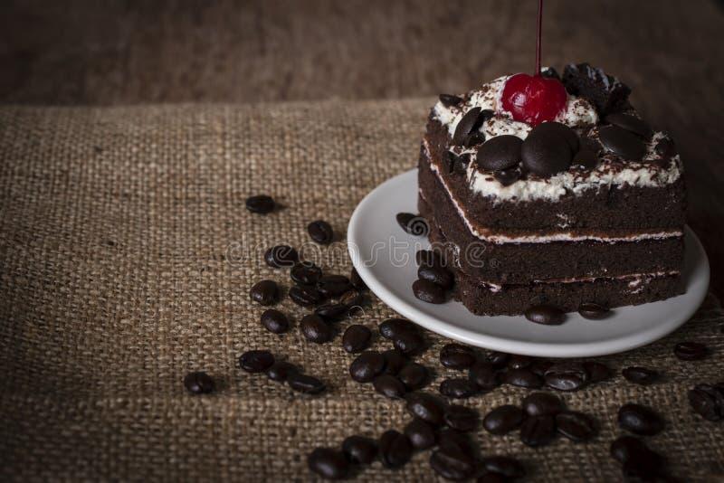 Schwarzer Forest Cake, der die Kirsche sich setzt auf die weiße Platte und die Kaffeebohnen gesetzt neben ihr übersteigt stockbild